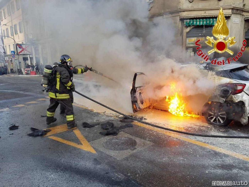 L'acqua dall'idrante sotto pressione utilizzata dai pompieri per domare l'incendio di un'auto